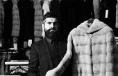 Man With Beard And Mustache Holds Fur Coat. Luxury Clothing Concept. Macho With Stylish Appearance W poster