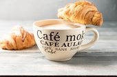 French Breakfast Is A Large Beige Cup Of Coffee With Milk And Croissants On A Wooden Table. On The C poster