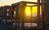 Silhouette Wooden With Blinds Gazebo On An Empty Sandy Beach On Sunset Background. poster