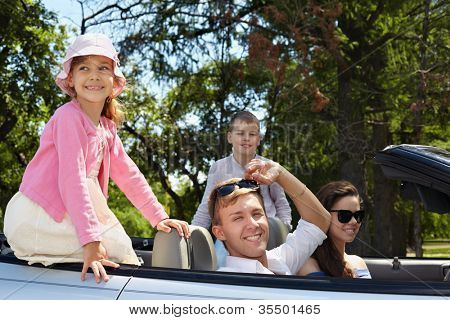 Young couple sits in cabriolet on front seats, boy sits on backseat, his younger sister sits on top of board of car