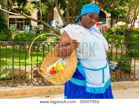 HAVANA-JULY 20:Unidentified woman dressed in typical clothes selling peanuts July 20,2012 in Havana.With the growth of tourism many people earn their living representing iconic traditional characters