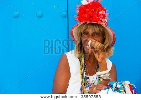 HAVANA-JULY 20:Unidentified old lady smokes a fine Cuban cigar July 20,2012 in Havana.The African culture have a huge influence in Cuba where approximately 50% of the population is of African descent