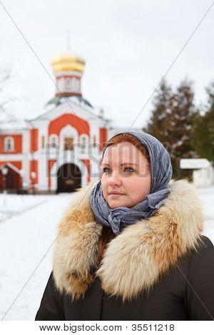 Peregrino ruso mujer en ropa de invierno contra el monasterio