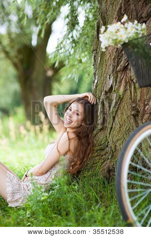 Woman sitting against tree