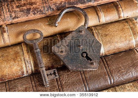 Open padlock and rusty key lying on ancient books