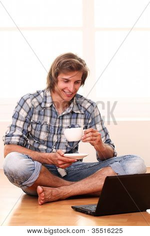 Handsome guy with a cup of coffee and laptop at home