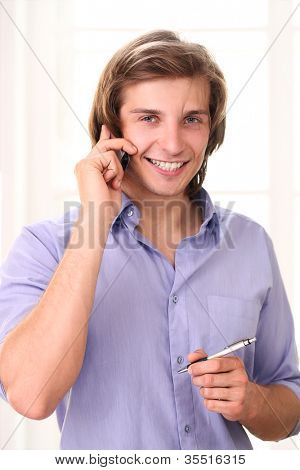 Handsome man calling by cell phone in his office