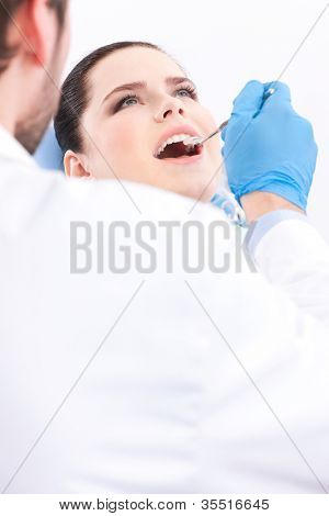Dentist in blue medical gloves examines the oral cavity of the patient, white background