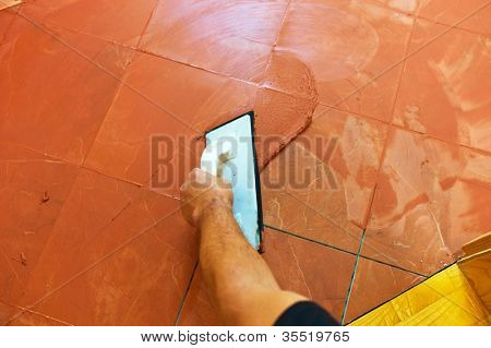 a tile carries on to the floor tile grout. grouting of tiles.