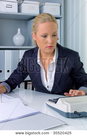 an accountant at work in the office with calculator