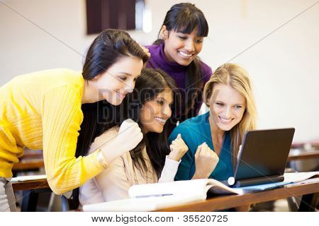 group of female college students cheering a game on laptop