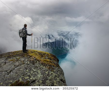 Homem com pé de equipamento para caminhadas na borda do rock