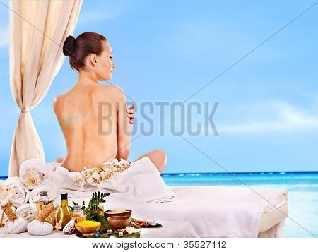 Young woman getting spa lastone therapy outdoor.