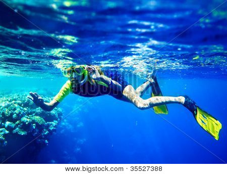 Child scuba diver with group coral fish in  blue water.
