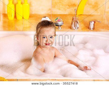 Little girl washing in bubble bath .