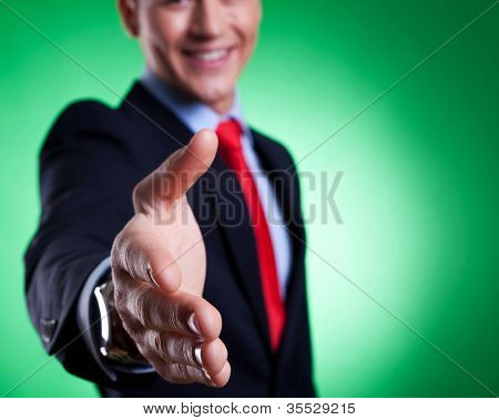 business man with an open hand ready for a handshake, closeup picture on green background