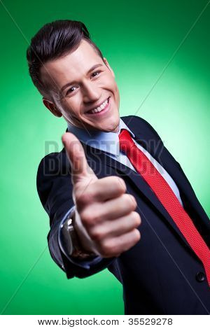 Happy business man on green background holding thumbs up ok sign
