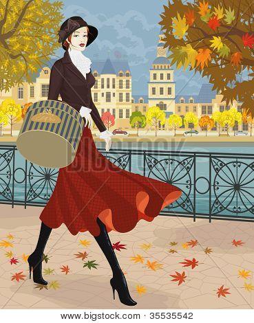 Beautiful young woman walking along embankment in autumn city