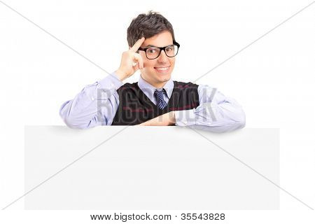 Young man standing behind white panel isolated on white background