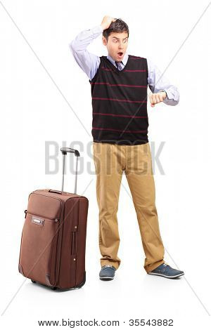 Full length portrait of a shocked man looking at his watch and his luggage, isolated on white background