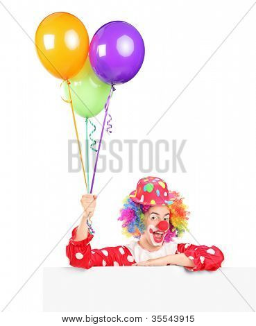 A male clown with happy joyful expression on his face posing behind a panel and holding balloons isolated on white background