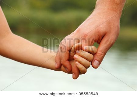 father's hand lead his child son against summer forest and river nature outdoor background, trust family concept