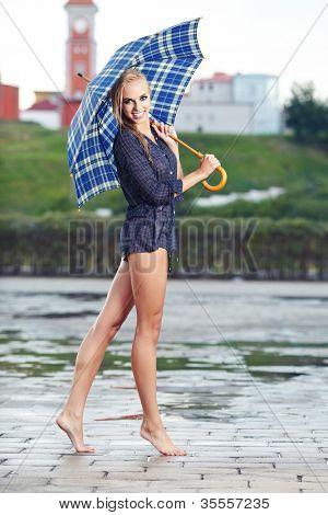 Chica sexy bajo paraguas mirando la lluvia