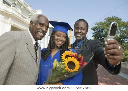 Happy female graduate with father and brother taking self-portrait through cell phone