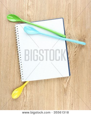 Open cookbook and kitchenware on wooden background