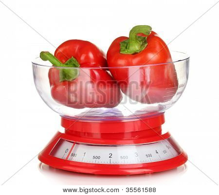 fresh red peppers in a kitchen scales isolated on white