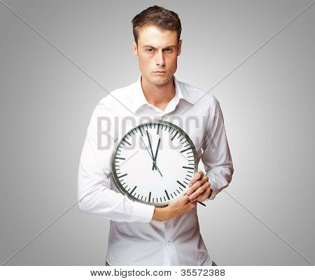 Portrait Of A Young Man Holding A Clock With His Hands On Gray Background