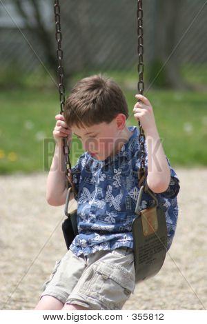 Boy Sad On Swing