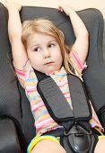 pic of seatbelt  - Small girl sitting in a car safety seat with seatbelt - JPG