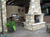 stock photo of chimney rock  - An outdoor fireplace on the back patio with chairs and a grill great for entertaining and relaxation