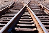 picture of train track  - Dual intersecting railroad tracks in an industrial setting.