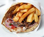 View of a pork souvlaki wrap, or pitta gyros,  incorporating fries, yoghurt and a salad or onion, to