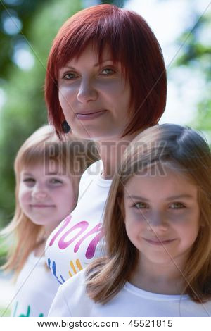 Young Mother And Her Cute Daughters Outdoors