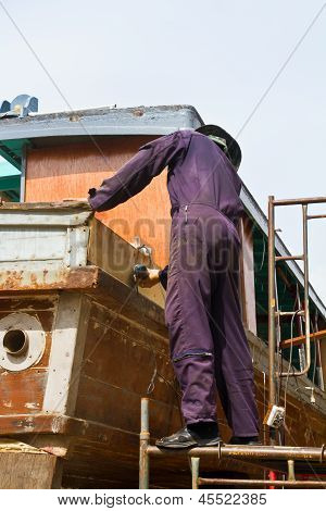 Carpenter is repairing boat in dry dock