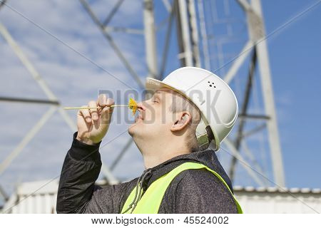 Engineer with a dandelion near the nose on gsm tower background