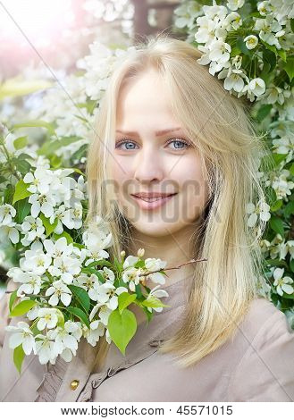 Beautiful  woman near blossom apple tree