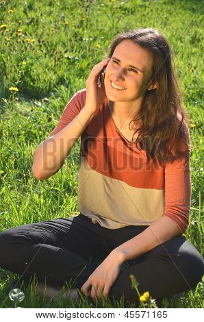 beautiful attractive brunette girl is sitting on a meadow and talking on mobile phone