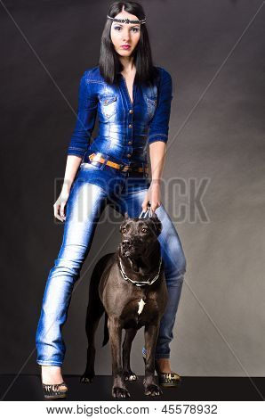 Beautiful woman in jeans clothes  standing next to a dog