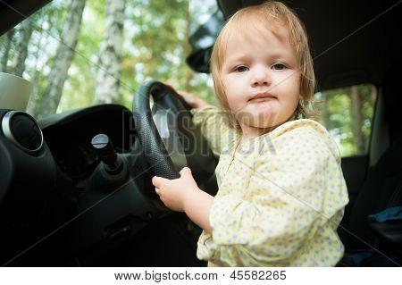 Little blond girl driving car
