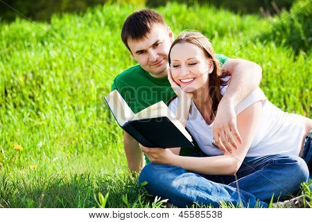 Couple Sitting In Park Reading Book