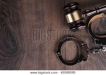 algemas e martelo de juiz em fundo de madeira