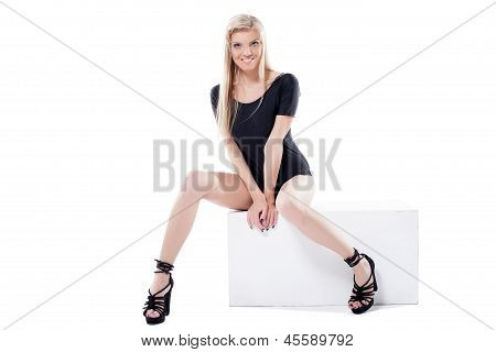 Cheerful leggy blonde posing on cube