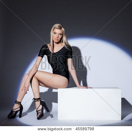 Attractive leggy blonde posing in spotlight