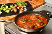 foto of hamburger-steak  - Hamburger steaks in tomato gravy simmering on hot electric stove with vegetables being prepared on wooden counter top - JPG