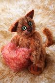 Cat Holding Fluffy Heart In His Paws On Fur Background poster