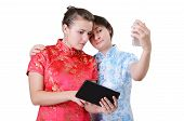 picture of gizmo  - Two Caucasian young women are standing and using a mobile phone and a pad - JPG